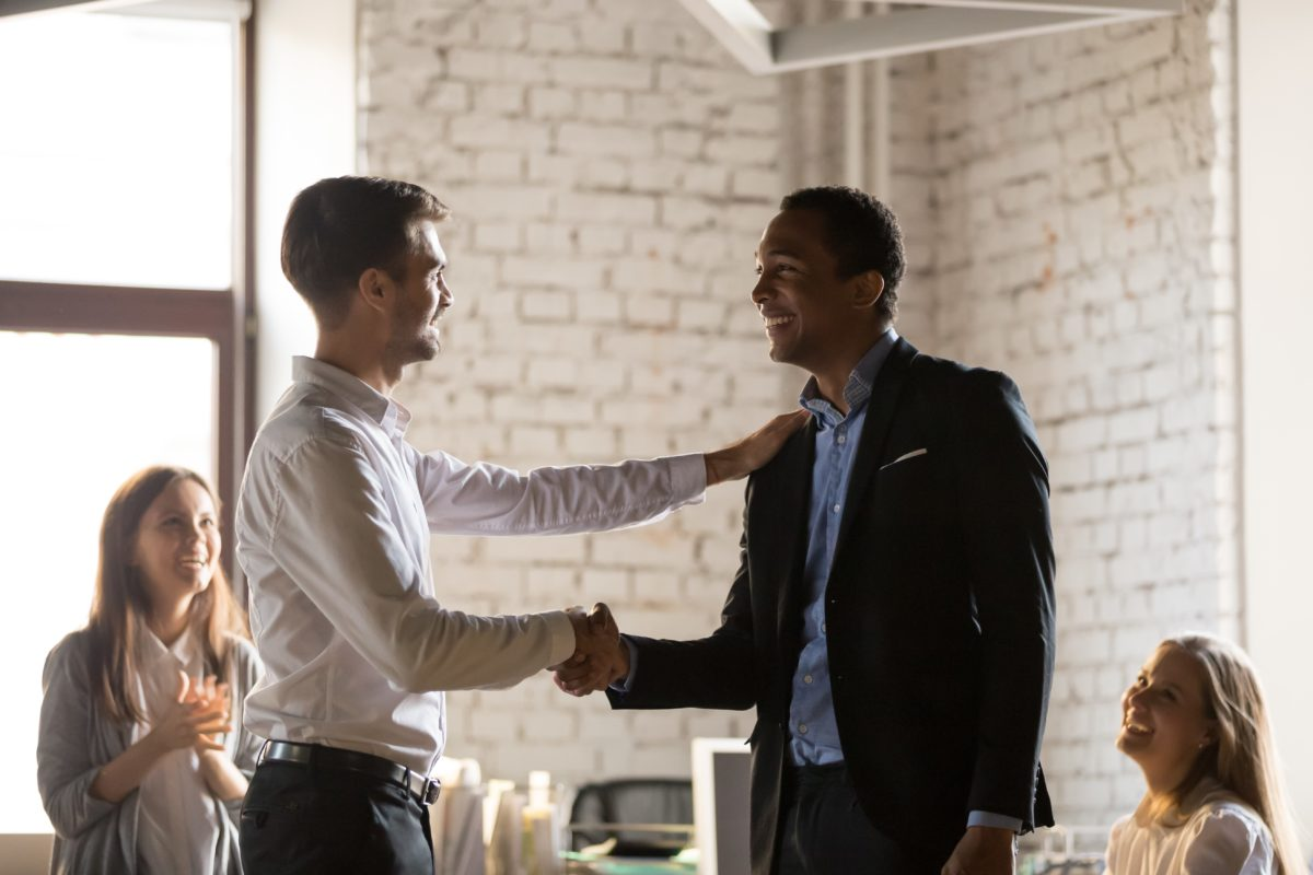 Two professionals shaking hands after a successful hire of a social media manager